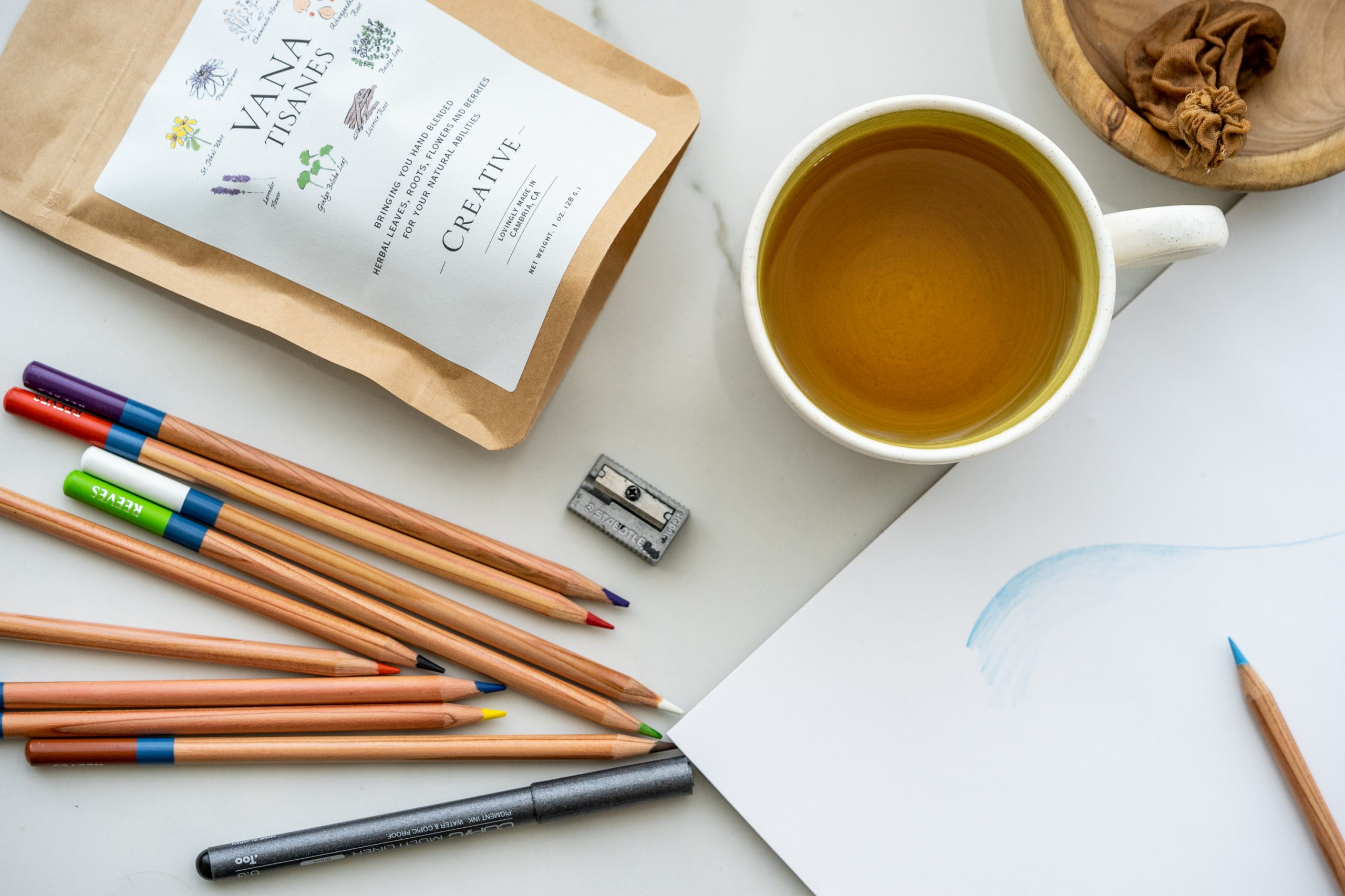 Photo of cup of brewed tea, art supplies and a sketchbook