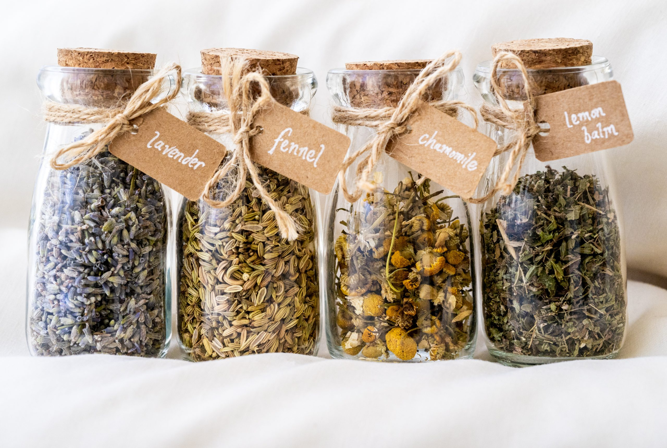 a photo of dried herbs in jars: lavender, fennel, chamomile, and lemon balm